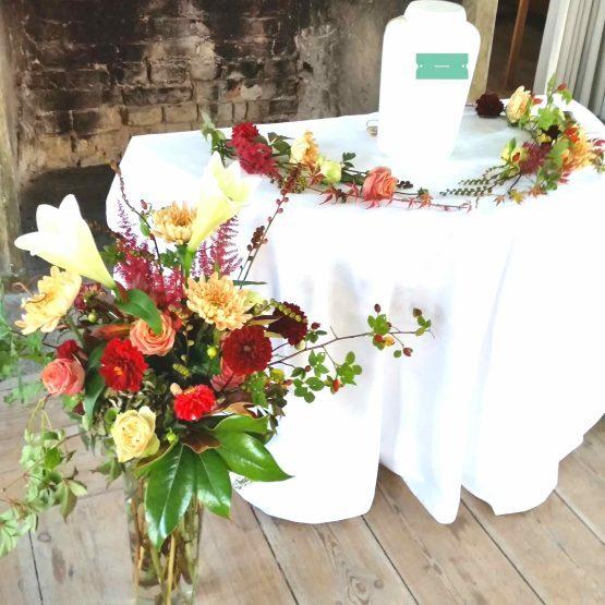 september urndekoration med blommor till begravning