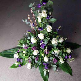 hög dekoration till begravning i lila och vitt