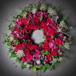 begravningskrans med röda rosor och ängsblommor