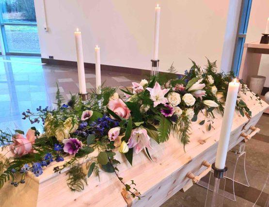 blommor arrangerade direkt på kistan